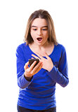 Surprised teenage girl with smartphone
