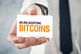 Businessman holding card with title WE ARE ACCEPTING BITCOINS