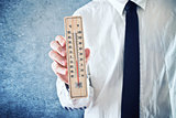 Businessman holding thermometer with temperature on Zero value