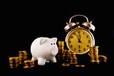 Golden coin stack, piggy coin bank and vintage clock on dark bac