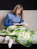 Girl reading book, covered with blanket on couch