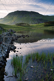 Beautiful sunrise mountain landscape reflected in calm lake