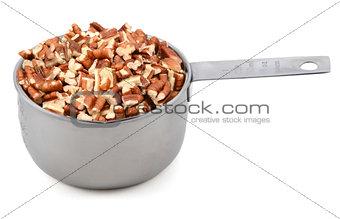 Chopped pecan nuts in a metal cup measure