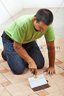 Construction worker testing the joint color on ceramic tiles flo