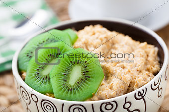 Bowl of oats porridge with kiwi
