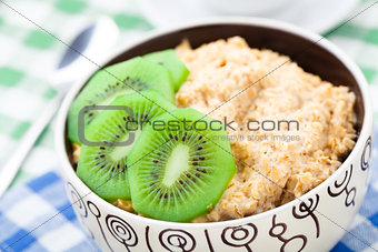 Bowl of oats porridge with kiwi