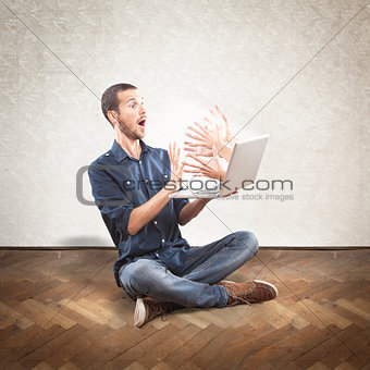Young scared man holding a laptop