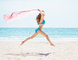 Young woman with parero jumping on beach