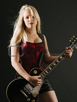 Blond woman playing electric guitar