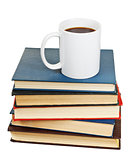white cup of coffee on stack of books