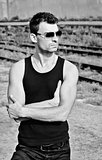 Fashion shot: portrait of handsome young man in black shirt wearing sunglasses. Black and white