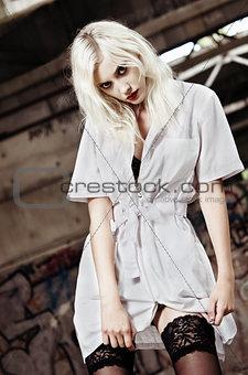 Beautiful strange nurse among industrial ruins