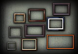 green grungy wall full of frames