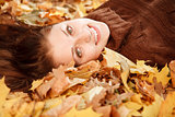 teenage girl lying down on leaves