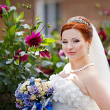 Young bride posing wigh flowers outside.
