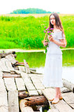 girl on an old wooden bridge with a bouquet of flowers
