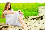 beautiful girl sits on an old wooden bridge