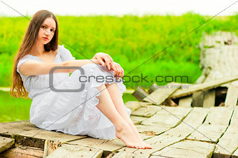 beautiful girl sits on an old wooden bridge
