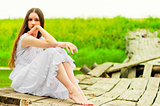 girl in a white sundress resting on the bridge