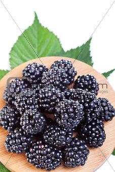 Blackberries on wooden plate