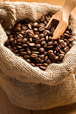 Coffee beans in canvas sack with wooden scoop