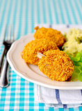 Cornflake crusted chicken pieces served with salad leaves and ma