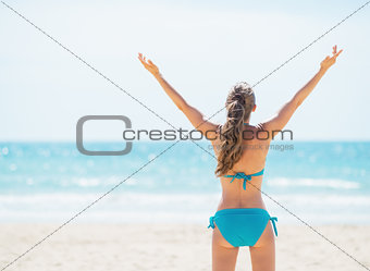 Portrait of smiling young woman rejoicing on beach. rear view
