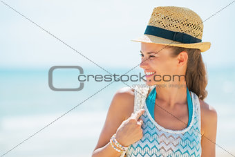 Portrait of smiling young woman in hat on beach looking on copy