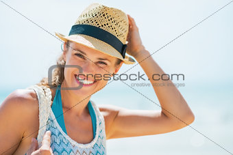 Portrait of happy young woman in hat on beach
