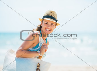 Portrait of happy young woman in hat and with bag on beach