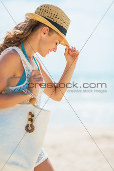 Portrait of young woman in hat and with bag on beach
