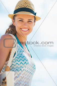 Portrait of happy young woman in hat and with bag