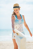 Happy young woman in hat and with bag having fun time on beach