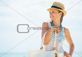 Portrait of young woman in hat and with bag looking on copy spac