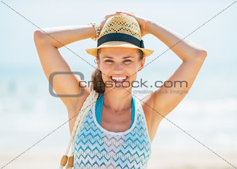 Portrait of smiling young woman in hat and with bag on beach
