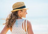 Young woman in hat and with bag on beach. rear view