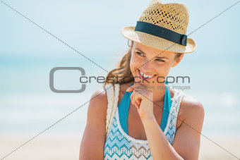 Portrait of smiling young woman in hat on beach
