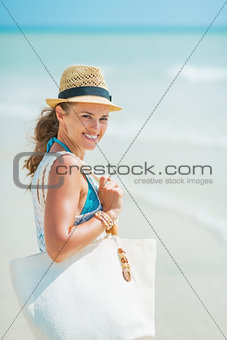 Portrait of happy young woman with hat and bag at seaside