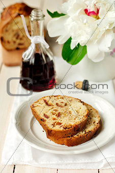 Slices of bergamot tea cake, a bottle of creme de cassis and a p