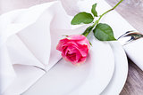 Table setting with a single pink rose