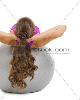 Fitness young woman making exercise on fitness ball. rear view