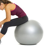 Closeup on fitness young woman sitting on fitness ball