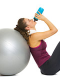 Fitness young woman sitting near fitness ball and drinking water