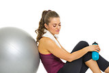Fitness young woman sitting near fitness ball with bottle of wat