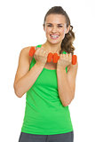 Smiling fitness young woman with dumbbells