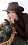 Cowgirl Relaxes in Brown Cowbooy Hat Leaning on Saddle With Rope