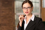 Business Woman Pauses Pen in Hand in Office Eyeglasses
