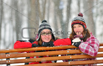 Two young girl friends together sitting on park bench