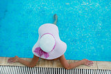 girl in a hat sitting in the water l