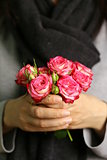bouquet of pink roses in female hands